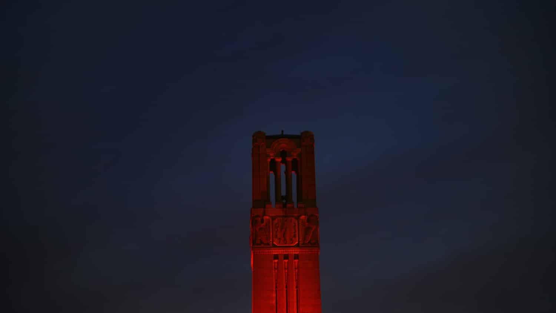 Belltower lit red against a night sky