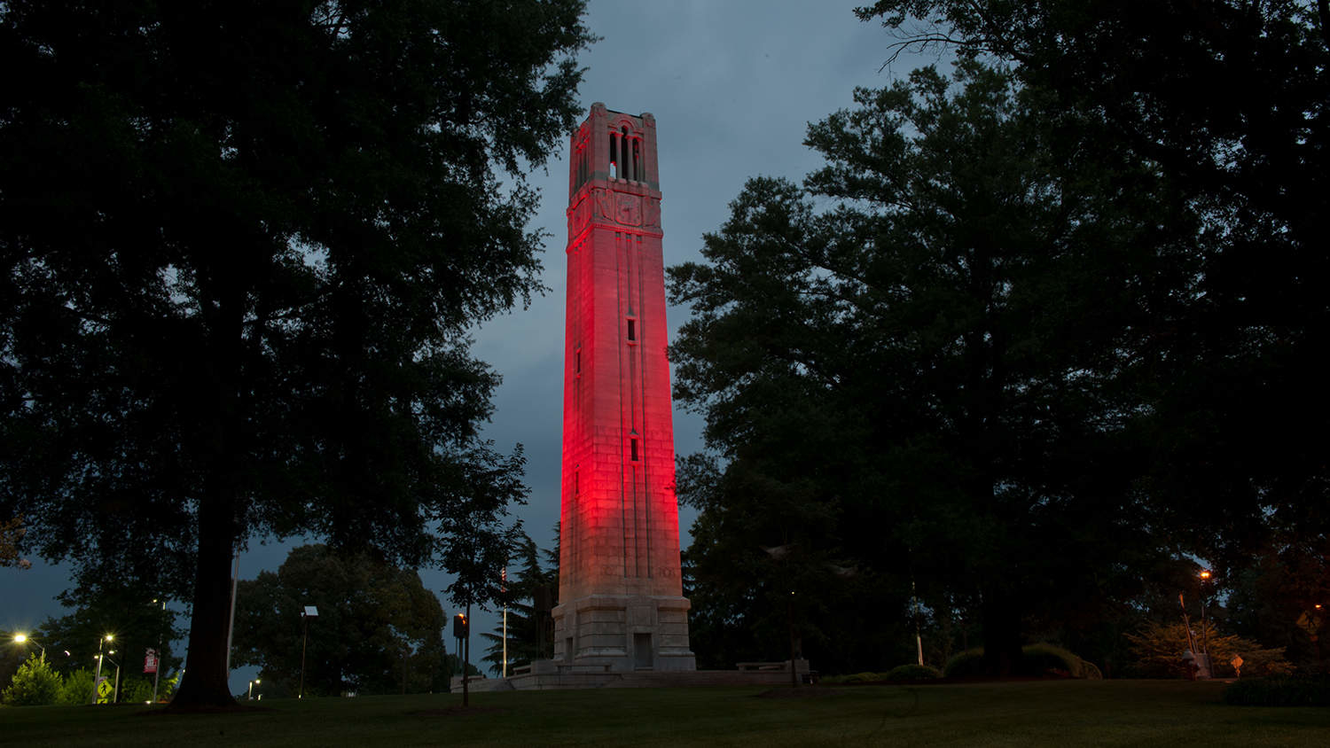 The NCState Belltower lit red against a night sky